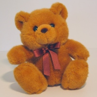 teddy bear and crimson bow around neck