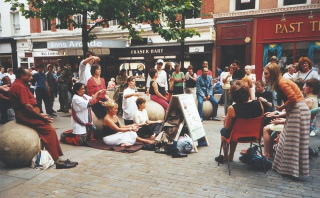 members of the public watch or participate in a street meditation workshop